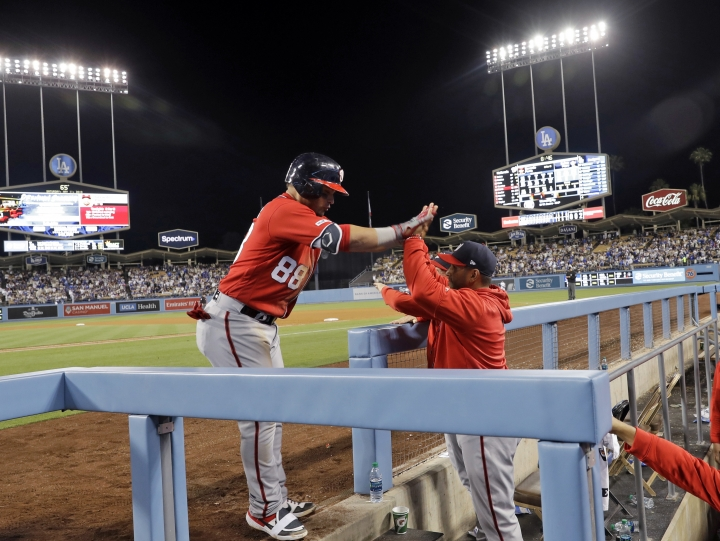 Washington Nationals' Gerardo Parra (88) is high-fived at the dugout by manager Dave Martinez after Parra's grand slam against the Los Angeles Dodgers during the eighth inning of a baseball game Saturday, May 11, 2019, in Los Angeles. (AP Photo/Marcio Jose Sanchez)