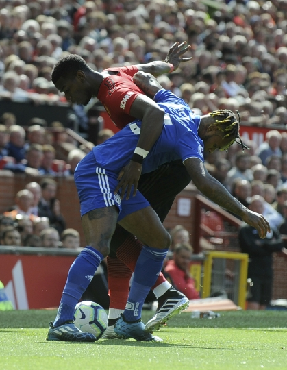Cardiff's Leandro Bacuna, front, duels for the ball with Manchester United's Paul Pogba during the English Premier League soccer match between Manchester United and Cardiff City at Old Trafford in Manchester, England, Sunday, May 12, 2019. (AP Photo/Rui Vieira)