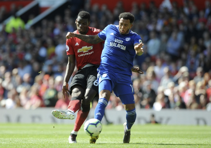 Manchester United's Paul Pogba, left, duels for the ball with Cardiff's Nathaniel Mendez-Laing during the English Premier League soccer match between Manchester United and Cardiff City at Old Trafford in Manchester, England, Sunday, May 12, 2019. (AP Photo/Rui Vieira)