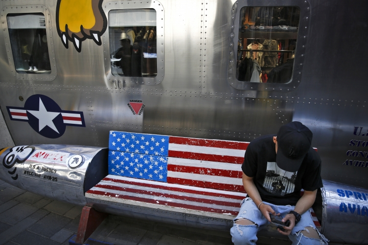A man browses his smartphone on a bench with a decorated with U.S. flag outside a fashion boutique selling U.S. brand clothing at the capital city's popular shopping mall in Beijing, Monday, May 13, 2019. Companies waited Monday to see how China decides to retaliate for President Donald Trump's latest tariff hike while forecasters warned their escalating fight over technology and trade might disrupt a Chinese economic recovery. (AP Photo/Andy Wong)
