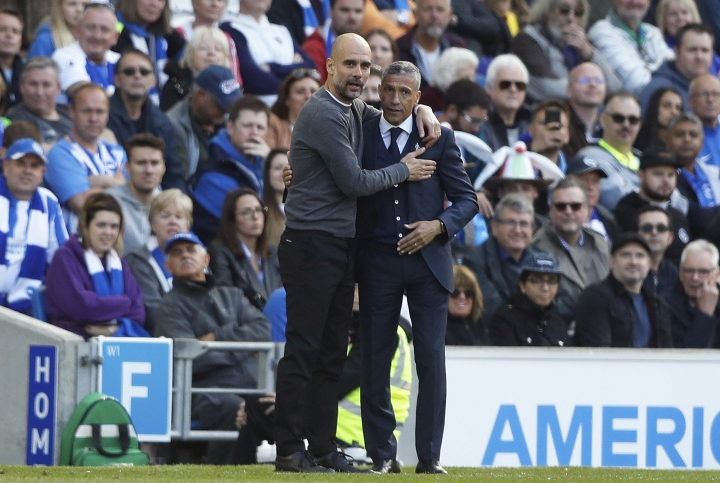 Manchester City coach Pep Guardiola and Brighton manager Chris Hughton, right, embrace each other during the English Premier League soccer match between Brighton and Manchester City at the AMEX Stadium in Brighton, England, Sunday, May 12, 2019. (AP Photo/Frank Augstein)