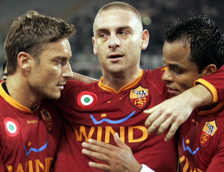 FILE - In this Jan. 16, 2008 file photo, Roma forward Francesco Totti, left, is hugged by teammats Daniele De Rossi, center, and Mancini after scoring during the Italy Cup soccer match between AS Roma and Torino at Rome's Olympic stadium. Roma captain Daniele De Rossi surprisingly announced on Tuesday, May 14, 2019 he is leaving his hometown club after 18 years.(AP Photo/Pier Paolo Cito, file)