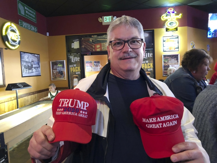 In this May 3, 2019 photo, Bruce Kudick shows off the Trump 2020 hats he bought during a Waukesha County GOP gathering in his hometown of New Berlin, Wis. Kudick, who retired but went back to work at a Wisconsin blood center, just got a raise and he's giving President Donald Trump credit for the strong economy. (AP Photo/Sara Burnett)