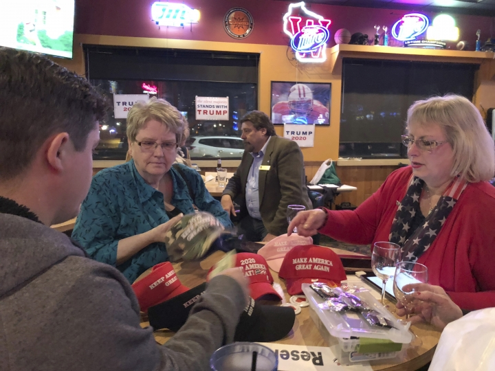 In this May 3, 2019 photo, Waukesha County GOP volunteers Wendy Radant, left, and Valerie Houk, right, sell Trump merchandise during a party gathering in New Berlin, Wis. The economy already is at the center of the 2020 fight for president, particularly in states like Wisconsin, Michigan and Pennsylvania that supported Trump in 2016 and that Democrats want to recapture next year. (AP Photo/Sara Burnett)
