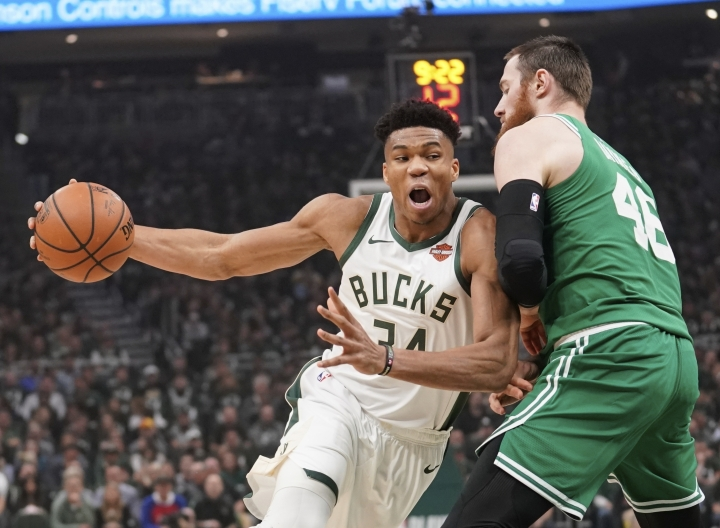 "File-This May 8, 2019, file photo shows Milwaukee Bucks' Giannis Antetokounmpo driving past Boston Celtics' Aron Baynes during the first half of Game 5 of a second round NBA basketball playoff series in Milwaukee. Leading the Bucks' resurgence is MVP candidate Antetokounmpo, a fan favorite and a source of pride for Milwaukee's Greek community. Antetokounmpo was born in Athens, Greece.""It's important for the Greek community to be able to gather together as a unit and celebrate him. And he in turn celebrates us,"" said Tim Stasinoulias, 61, a Bucks fan since the team came to Milwaukee in 1968.(AP Photo/Morry Gash, File)"
