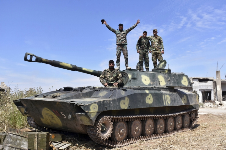 In this photo released by the Syrian official news agency SANA, Syrian army soldiers flash the victory sign as they stand on their tank in the village of Kfar Nabuda, in the countryside of the Hama province on Saturday, May 11, 2019. The Britain-based Syrian Observatory for Human Rights said government forces are now in control of nine villages forming an L shape at the far southern corner of the rebel stronghold. The villages include the strategic village of Kfar Nabuda and the elevated Qalaat Madiq, giving the government troops an advantage over the insurgents. (SANA via AP)