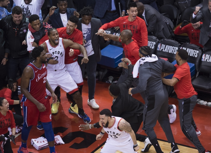 Toronto Raptors forward Kawhi Leonard (2) reacts with teammates after making a shot to defeat the Philadelphia 76ers at the end of the second half of an NBA Eastern Conference semifinal basketball game in Toronto on Sunday, May 12, 2019. (Nathan Denette/The Canadian Press via AP)