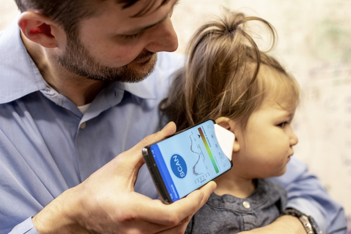 "In this undated photo provided by the University of Washington in May 2019, Dr. Randall Bly uses a uses a phone app and a paper funnel to focus the sound, to check his daughter for an ear infection, at the UW School of Medicine in Seattle. Bly and other researchers at the school have developed the system to ""hear"" a warning sign of ear infections _ fluid build-up behind the eardrum. (Dennis Wise/University of Washington via AP)"