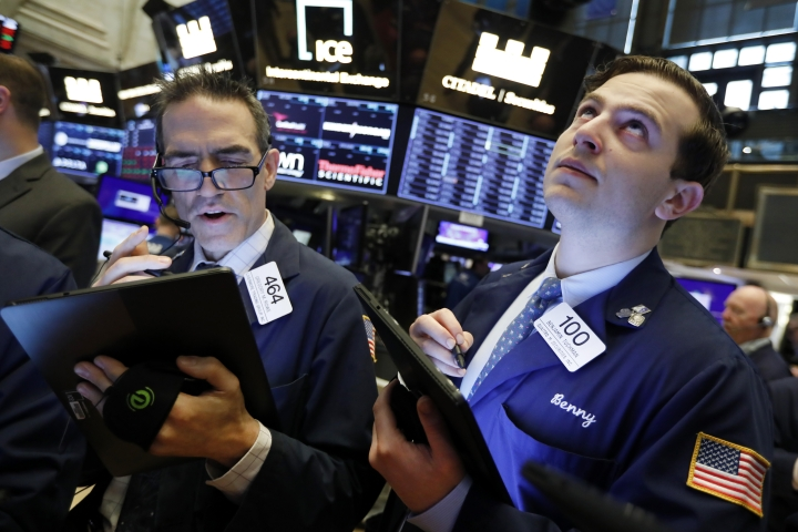 FILE - In this May 9, 2019, file photo traders Gregory Rowe and Benjamin Tuchman work on the floor of the New York Stock Exchange. The U.S. stock market opens at 9:30 a.m. EDT on Wednesday, May 15. (AP Photo/Richard Drew, File)