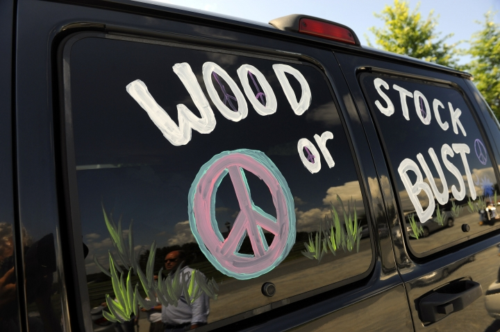 "FILE - This Aug. 14, 2009 file photo shows a van decorated with ""Woodstock or Bust"" at the original Woodstock Festival site in Bethel, N.Y. The Woodstock 50 festival is back on after a court on Wednesday, May 15, 2019 rebuffed an ex-investor's effort to cancel the anniversary extravaganza. But organizers will have to do without some $18 million, at least for now. (AP Photo/Stephen Chernin, File)"