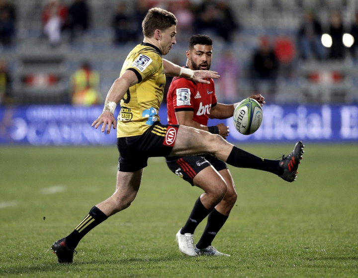 FILE - In this July 28, 2018, file photo, the Hurricanes' flyhalf Beauden Barrett, left, kicks at the ball as the Crusaders' flyhalf Richie Mo'unga watches during their Super Rugby semifinal in Christchurch, New Zealand. The importance of flyhalves to success in Super Rugby is well documented over the tournament's 23-year history. The influence of flyhalves on matches this 2019 season, demonstrated again in the weekend's 13th round, heavily underscores the established truth of their influence. (AP Photo/Mark Baker, File)