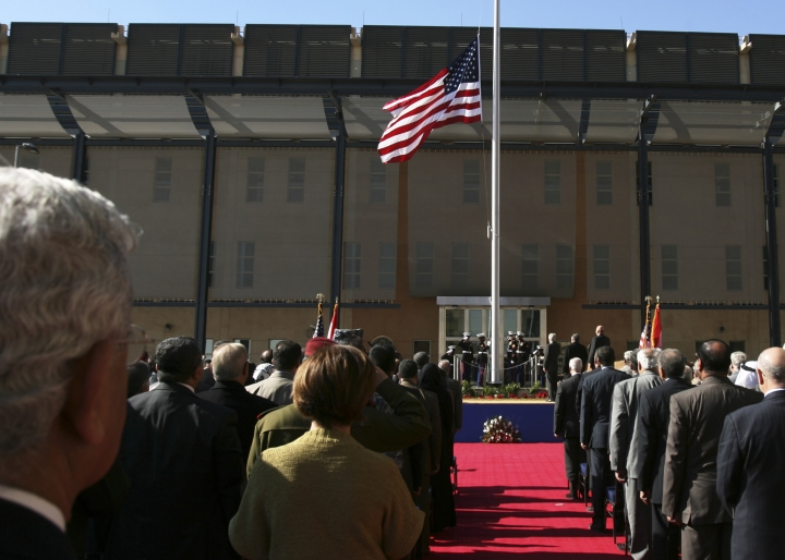 FILE - In this Jan. 5, 2009 file photo, people watch the U.S. flag as it is raised during a ceremony marking the opening of the new U.S. Embassy in Baghdad, Iraq. On Wednesday, May 15, 2019, the U.S. Embassy in Baghdad ordered all non-essential, non-emergency government staff to leave Iraq immediately amid escalating tensions with Iran. (AP Photo/Hadi Mizban, File)