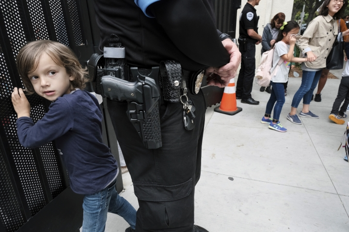 In this Monday May 13, 2019 photo Julian Richner, 9, leaves school for the day to meet his mother as he passes behind a security guard at Beverly Hills Unified School District's K-8 Horace Mann School in Beverly Hills, Calif. Districts nationwide are employing a multi-layered approach that combines mental health programs, bullying prevention initiatives with hardware and software technology, as well as armed and unarmed security officers. Beverly Hills Unified School District is one such district. (AP Photo/Richard Vogel)
