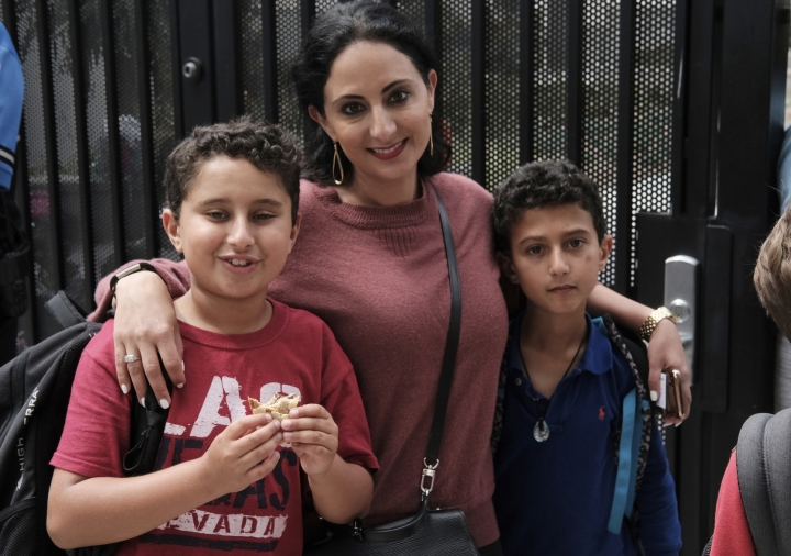 """In this Monday May 13, 2019 photo Evelyn Lahiji, picks up her sons, after school second-grader Lorenzo Naghdechi, 8, right, and third-grader Leonardo Naghdechi, 9, at Horace Mann School in Beverly Hills, Calif. Lahiji, said """"I'm grateful I live in this community that has so much security and I know they are protected."""" Schools in Beverly Hills and others nationwide are adopting a strategy that aims to speed up the law enforcement response to shootings. (AP Photo/Richard Vogel)"""