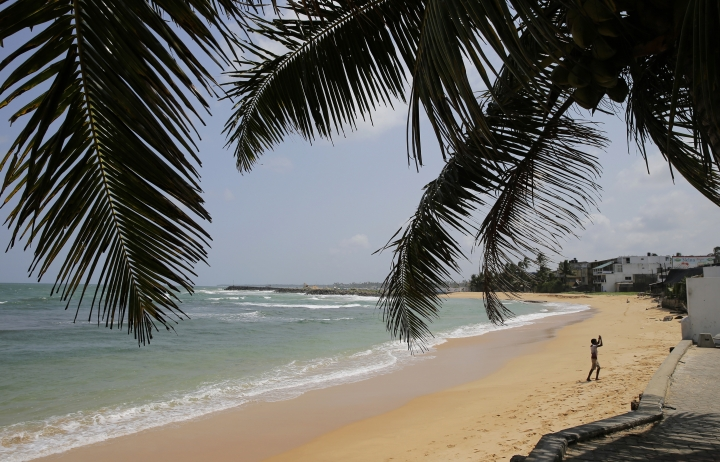 In this Friday, May 10, 2019, photo, a boy walks on a beach in Hikkaduwa, Sri Lanka. Sri Lanka was the Lonely Planet guide's top travel destination for 2019, but since the Easter Sunday attacks on churches and luxury hotels, foreign tourists have fled. Hikkaduwa, in the south west, used to be top tourist attraction for the strong waves that were perfect for board-surfing and sparkling clear waters perfect for snorkeling. Today, of the 27 hotels, a very few are still open while most of others along with the eateries lining the six kilometer stretch of palm-fringed beach, are closed. (AP Photo/Eranga Jayawardena)
