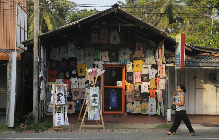In this Friday, May 10, 2019, photo, a Sri Lankan walks past a souvenir shop in Hikkaduwa, Sri Lanka. Sri Lanka was the Lonely Planet guide's top travel destination for 2019, but since the Easter Sunday attacks on churches and luxury hotels, foreign tourists have fled. Hikkaduwa, in the south west, used to be top tourist attraction for the strong waves that were perfect for board-surfing and sparkling clear waters perfect for snorkeling. Today, of the 27 hotels, a very few are still open while most of others along with the eateries lining the six kilometer stretch of palm-fringed beach, are closed. (AP Photo/Eranga Jayawardena)