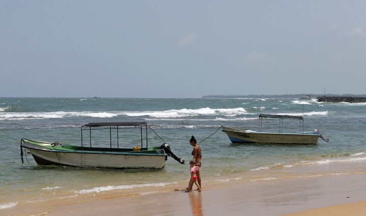 In this Friday, May 10, 2019, photo, a Ukrainian woman and a child walk past glass bottom boats, used for watching coral reefs, on a beach in Hikkaduwa, Sri Lanka. Sri Lanka was the Lonely Planet guide's top travel destination for 2019, but since the Easter Sunday attacks on churches and luxury hotels, foreign tourists have fled. Hikkaduwa, in the south west, used to be top tourist attraction for the strong waves that were perfect for board-surfing and sparkling clear waters perfect for snorkeling. Today, of the 27 hotels, a very few are still open while most of others along with the eateries lining the six kilometer stretch of palm-fringed beach, are closed. (AP Photo/Eranga Jayawardena)