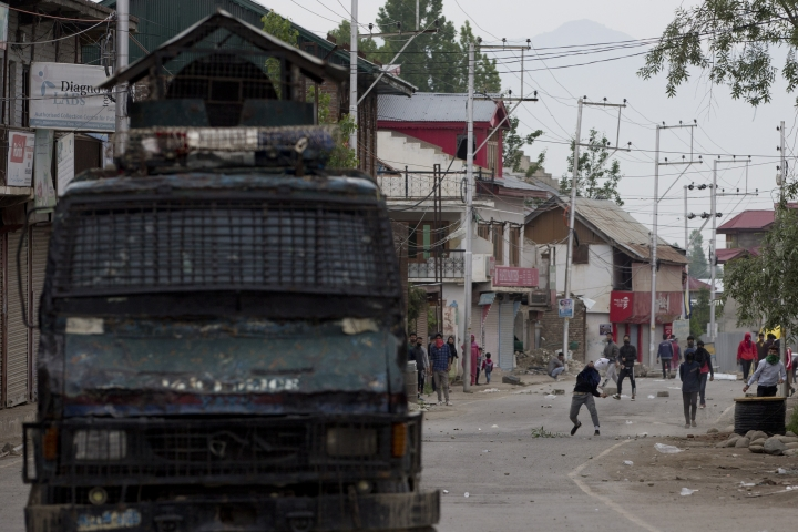 Kashmir protesters throw stones and bricks at an armored vehicle of Indian police during a protest near the site of a gunbattle in Pulwama, south of Srinagar, Indian controlled Kashmir, Thursday, May 16, 2019. Three rebels, an army soldier and a civilian were killed early Thursday during a gunbattle in disputed Kashmir that triggered anti-India protests and clashes, officials and residents said. (AP Photo/ Dar Yasin)