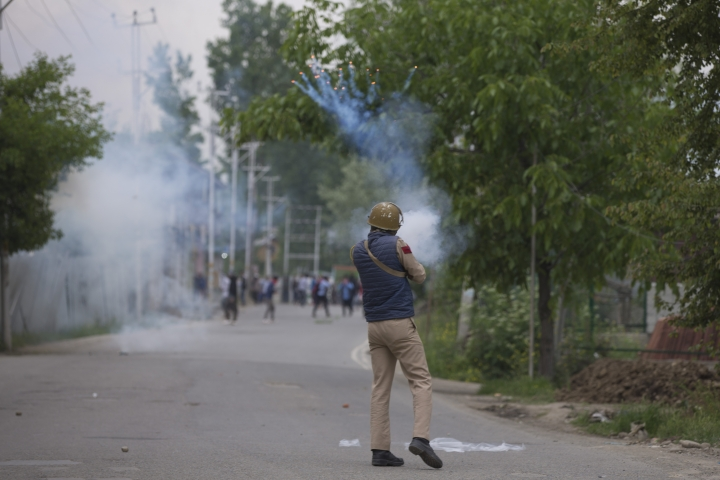 An Indian police man fires tear gas shell at Kashmir protesters near the site of a gunbattle in Pulwama, south of Srinagar, Indian controlled Kashmir, Thursday, May 16, 2019. Three rebels, an army soldier and a civilian were killed early Thursday during a gunbattle in disputed Kashmir that triggered anti-India protests and clashes, officials and residents said. (AP Photo/ Dar Yasin)
