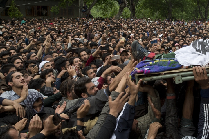 Kashmiri villagers try to touch the feet of top rebel commander Naseer Pandith, during his funeral procession in Pulwama, south of Srinagar, Indian controlled Kashmir, Thursday, May 16, 2019. Three rebels, an army soldier and a civilian were killed early Thursday during a gunbattle in disputed Kashmir that triggered anti-India protests and clashes, officials and residents said.(AP Photo/ Dar Yasin)