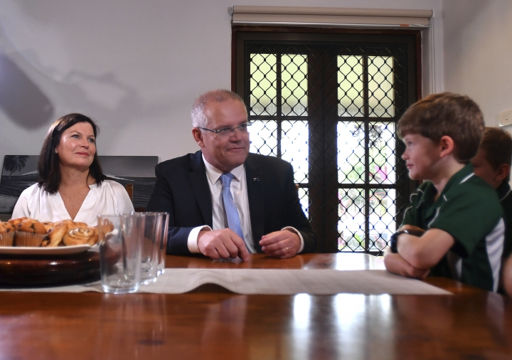 Australian Prime Minister Scott Morrison, center, meets with a family saving for their first home in Cairns, Australia Friday, May 17, 2019. A federal election will be held in Australian on Saturday May 18, 2019. (Mick Tsikas/AAP Image via AP)