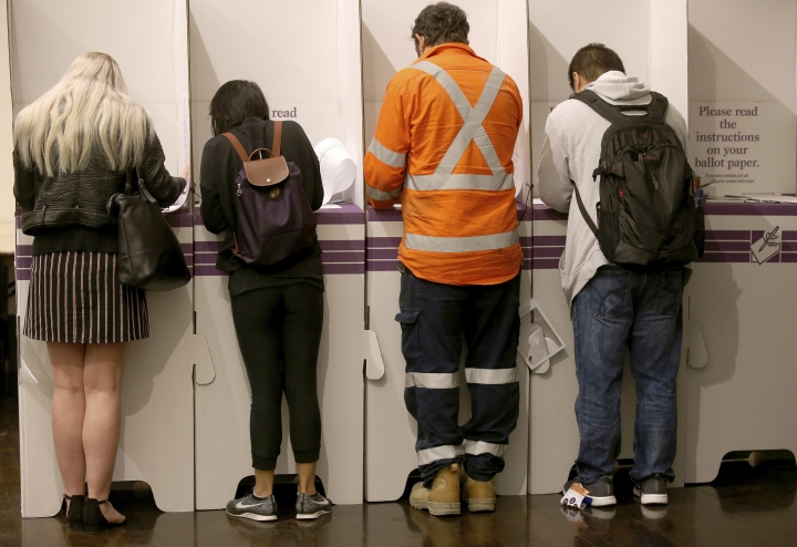 Voters fill in their ballots at Town Hall in Sydney, Australia, in a federal election, Saturday, May 18, 2019. Polling stations have opened in eastern Australia on Saturday in elections that are likely to deliver the nation's sixth prime minister in as many years. (AP Photo/Rick Rycroft)