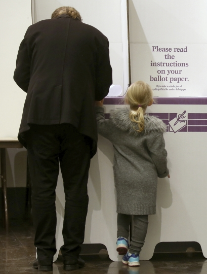A young girl waits as a voter fills in their ballot at Town Hall in Sydney, Australia, in a federal election, Saturday, May 18, 2019. Polling stations have opened in eastern Australia on Saturday in elections that are likely to deliver the nation's sixth prime minister in as many years. (AP Photo/Rick Rycroft)