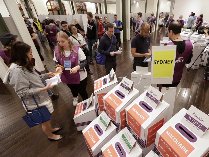Voters cast their ballots at the Town Hall in Sydney, Australia, in a federal election, Saturday, May 18, 2019. Polling stations have opened in eastern Australia on Saturday in elections that are likely to deliver the nation's sixth prime minister in as many years. (AP Photo/Rick Rycroft)