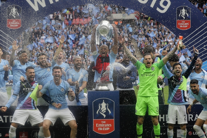 Manchester City players celebrate with the trophy after the English FA Cup Final soccer match between Manchester City and Watford at Wembley stadium in London, Saturday, May 18, 2019. (AP Photo/Kirsty Wigglesworth)