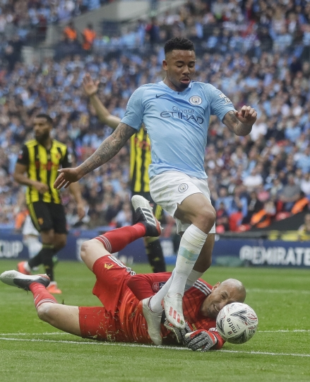Watford's goalkeeper Heurelho Gomes tries to stop Manchester City's Gabriel Jesus during the English FA Cup Final soccer match between Manchester City and Watford at Wembley stadium in London, Saturday, May 18, 2019. (AP Photo/Kirsty Wigglesworth)