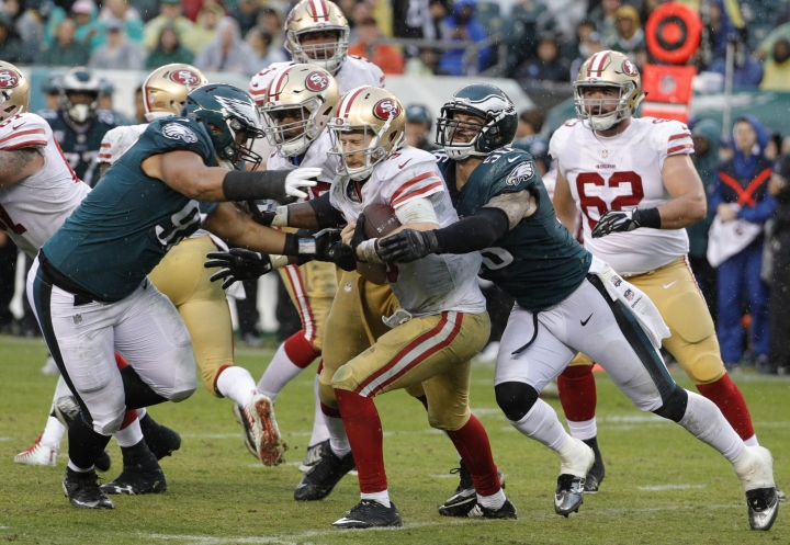"""FILE - In this Oct. 29, 2017, file photo, Philadelphia Eagles' Destiny Vaeao (97) and Chris Long (56) take down San Francisco 49ers' C.J. Beathard during the second half of an NFL football game in Philadelphia. Long has announced his retirement from football, ending an 11-year NFL playing career that included winning two Super Bowl titles and the Walter Payton Man of the Year Award. Long posted his decision Saturday night, May 18, on Twitter, saying it has """"been a hell of a journey"""" and adds that """"I can honestly say I put my soul into every minute of it."""" (AP Photo/Chris Szagola, File)"""