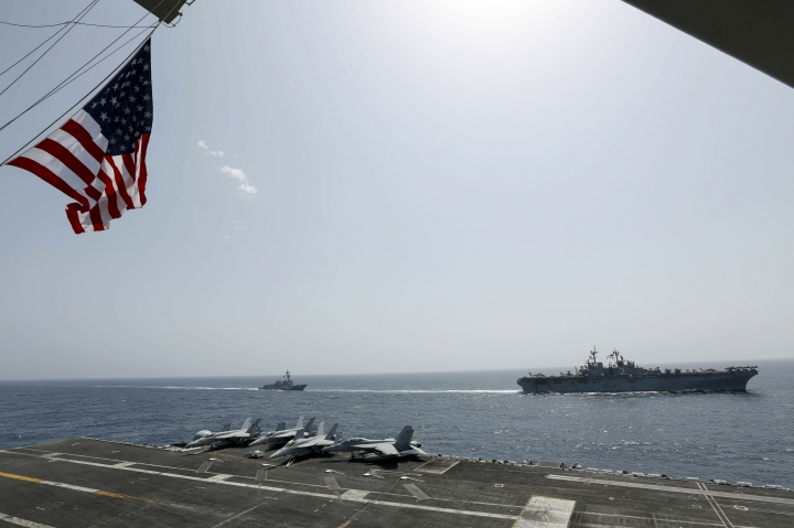 """CORRECTS DATE - In this Friday, May 17, 2019, photo, released by the U.S. Navy, the amphibious assault ship USS Kearsarge, right, and the Arleigh Burke-class guided-missile destroyer USS Bainbridge, left, are seen from the Nimitz-class aircraft carrier USS Abraham Lincoln as they sail in the Arabian Sea. Commercial airliners flying over the Persian Gulf risk being targeted by """"miscalculation or misidentification"""" from the Iranian military amid heightened tensions between the Islamic Republic and the U.S., American diplomats warned Saturday, May 18, 2019, even as both Washington and Tehran say they don't seek war. (Mass Communication Specialist Seaman Michael Singley, U.S. Navy via AP)"""