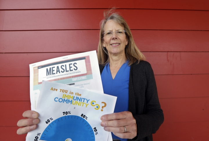"""In this photo taken Wednesday, May 15, 2019, Vashon Island High School nurse Sarah Day holds information about measles vaccinations as she poses for a photo in Vashon Island, Wash. Since Day began communal living on Vashon Island more than 20 years ago, the registered nurse has been advocating for getting kids their shots against a loud contingent of anti-vaccine parents in the close-knit community of about 11,000 that's accessible only by ferry, a serene 20-minute ride from Seattle. And it may now be working, thanks to a """"perfect storm"""" of changes being felt on the island, Day said. (AP Photo/Elaine Thompson)"""