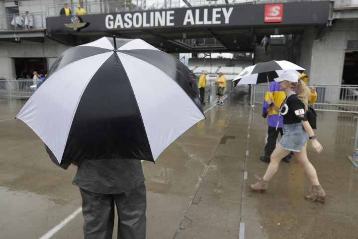 Fans walk past the garage area as rain delays the final portion of qualifications for the Indianapolis 500 IndyCar auto race at Indianapolis Motor Speedway, Sunday, May 19, 2019 in Indianapolis. (AP Photo/Michael Conroy)