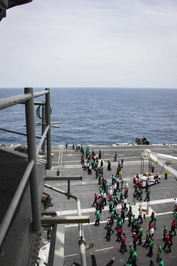 ADDS LOCATION - In this Sunday, May 19, 2019, photo released by the U.S. Navy, sailors partake in a foreign object and debris walk-down on the flight deck of the Nimitz-class aircraft carrier USS Abraham Lincoln in the Arabian Sea. (Mass Communication Specialist 3rd Class Garrett LaBarge/U.S. Navy via AP)