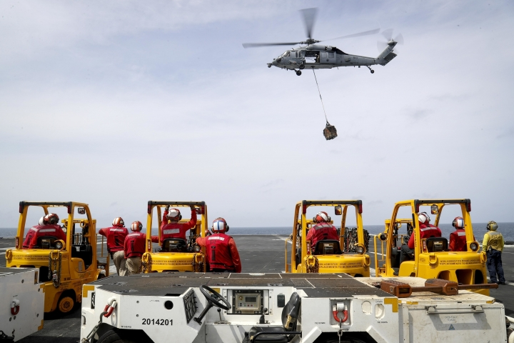 "In this Sunday, May 19, 2019, photo released by the U.S. Navy, an MH-60S Sea Hawk helicopter from the ""Nightdippers"" of Helicopter Sea Combat Squadron 5 transports cargo from the fast combat support ship USNS Arctic to the Nimitz-class aircraft carrier USS Abraham Lincoln during a replenishment-at-sea in the Arabian Sea. (Mass Communication Specialist 3rd Class Jeff Sherman/U.S. Navy via AP)"