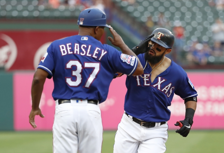 Texas Rangers third base coach Tony Beasley (37) salutes Rougned Odor, right, as Odor rounds the bag on his way home after hitting a three-run home run off of Seattle Mariners starting pitcher Mike Leake in the first inning of a baseball game in Arlington, Texas, Monday, May 20, 2019. The shot also scored Joey Gallo and Nomar Mazara. (AP Photo/Tony Gutierrez)