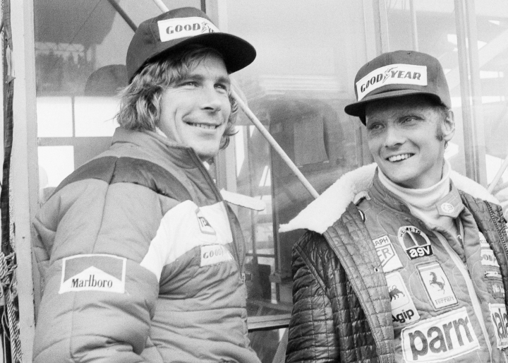 """FILE - In this Oct. 24, 1976, file photo, Austrian auto racer Niki Lauda, right, defending champion in world driving, and James Hunt, of Britain, look at the rain before the start of the Japan Grand Prix Formula One auto race at Fuji International Speedway, Gotemba, Japan. Three-time Formula One world champion Niki Lauda, who won two of his titles after a horrific crash that left him with serious burns and went on to become a prominent figure in the aviation industry, has died. He was 70. The Austria Press Agency reported Lauda's family saying in a statement he """"passed away peacefully"""" on Monday, May 20, 2019. (AP Photo/Nick Ut, File)"""