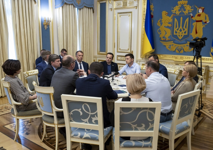 Ukrainian president Volodymyr Zelenskiy, center, speaks during a meeting with lawmakers in Kiev, Ukraine, Tuesday, May 21, 2019. Zelenskiy dropped a bombshell when he said he is dissolving the parliament, dominated by allies of the former Ukrainian president. Zelenskiy sat down with political leaders Tuesday morning to discuss the dissolution. (Ukrainian Presidential Press Office via AP)