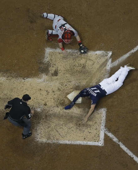 Milwaukee Brewers' Mike Moustakas slides safely past Cincinnati Reds catcher Tucker Barnhart during the fourth inning of a baseball game Wednesday, May 22, 2019, in Milwaukee. (AP Photo/Morry Gash)