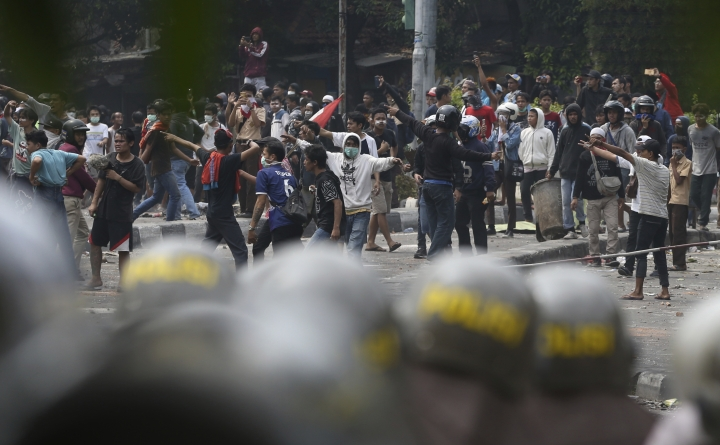 Supporters of the losing presidential candidate clash with police Wednesday, May 22, 2019, in Jakarta, Indonesia. A number of people have died and dozens of vehicles burned as rioters took over neighborhoods in central Jakarta, throwing rocks and Molotov cocktails at police who responded with tear gas, water cannon and rubber bullets.. (AP Photo/Achmad Ibrahim)