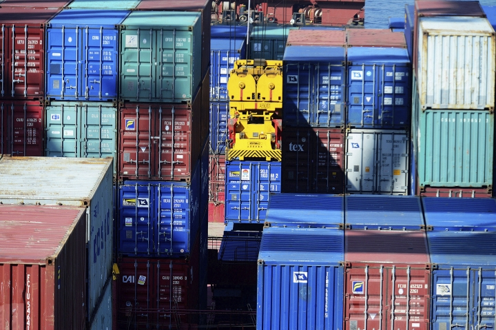 "In this Thursday, May 23, 2019, photo, a crane lifts a shipping container at a port in Qingdao in eastern China's Shandong province. Stepping up a propaganda offensive against Washington, China's state media on Friday accused the U.S. of seeking to ""colonize global business"" by targeting telecom equipment giant Huawei and other Chinese companies. (Chinatopix via AP)"