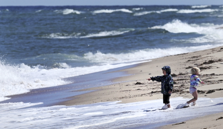 In this May 22, 2019, photo, two children play in the surf at Newcomb Hollow Beach, where a boogie boarder was bitten by a shark and later died of his injuries the previous summer, in Wellfleet, Mass. Cape Cod beaches open this holiday weekend, just months after two shark attacks, one of which was fatal, rattled tourists, locals and officials. Some precautionary new measures, such as emergency call boxes, have yet to be installed along beaches where great whites are known to frequent. (AP Photo/Charles Krupa)