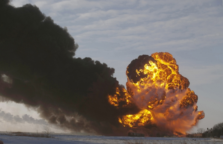 FILE - In this Dec. 30, 2013 file photo, a fireball goes up at the site of an oil train derailment near Casselton, N.D. The Trump administration is withdrawing a proposal for freight trains to have at least two crew members that was drafted in response to explosions of crude oil trains in the U.S. and Canada. Transportation officials said Thursday, May 23, 2019 that a review of accident data did not support the notion that having one crew member is less safe than a multi-person crew. (AP Photo/Bruce Crummy, File)