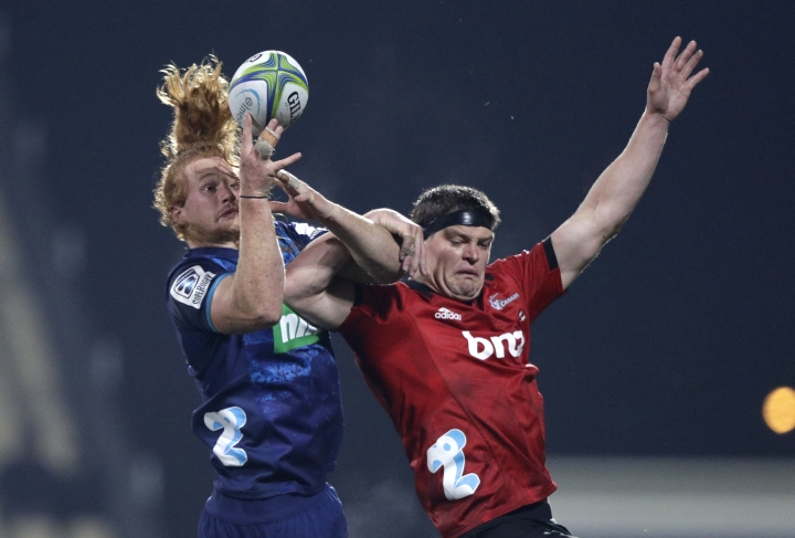 Blues Tom Robinson, left, and Crusaders Scott Barrett battle for the ball during their Super Rugby match in Christchurch, New Zealand, Saturday, May 25, 2019. (AP Photo/Mark Baker)