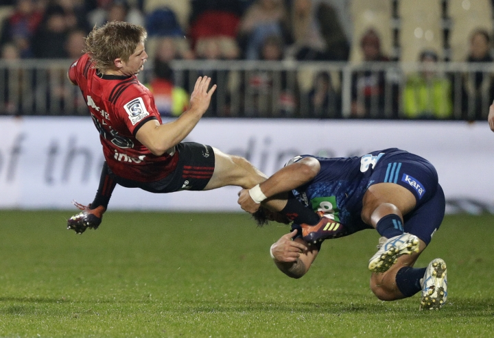 Crusaders Jack Goodhue, left, is airborne as he is tackled by Blues Levi Aumua during their Super Rugby match in Christchurch, New Zealand, Saturday, May 25, 2019. (AP Photo/Mark Baker)