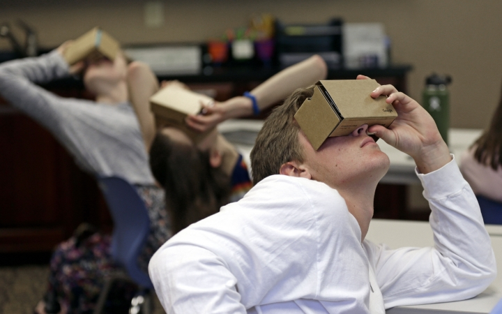 """In this photo taken Tuesday, May 21, 2019, photo, Zane Taylor and other students use virtual reality technology to learn about the D-Day invasion at Normandy during a history class at Crossroads FLEX school in Cary, N.C. Its 75th anniversary brings extra classroom attention to D-Day, which has waned as a topic that's emphasized in schools across the world. In a North Carolina classroom, students learn about spies, the deadly military practice before D-Day and a general who kept his plans """"on the down low."""" (AP Photo/Gerry Broome)"""