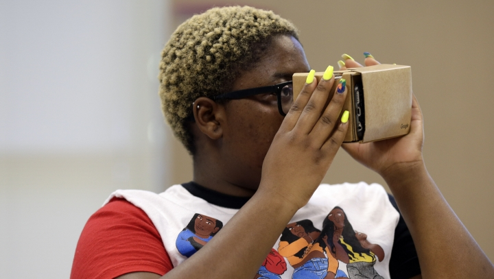 "In this photo taken Tuesday, May 21, 2019, Nydasia Lewis uses a virtual reality visual aid along with fellow 11th grade students learning about the D-Day invasion at Normandy during a history class at Crossroads FLEX school in Cary, N.C. Its 75th anniversary brings extra classroom attention to D-Day, which has waned as a topic that's emphasized in schools across the world. In a North Carolina classroom, students learn about spies, the deadly military practice before D-Day and a general who kept his plans ""on the down low."" (AP Photo/Gerry Broome)"
