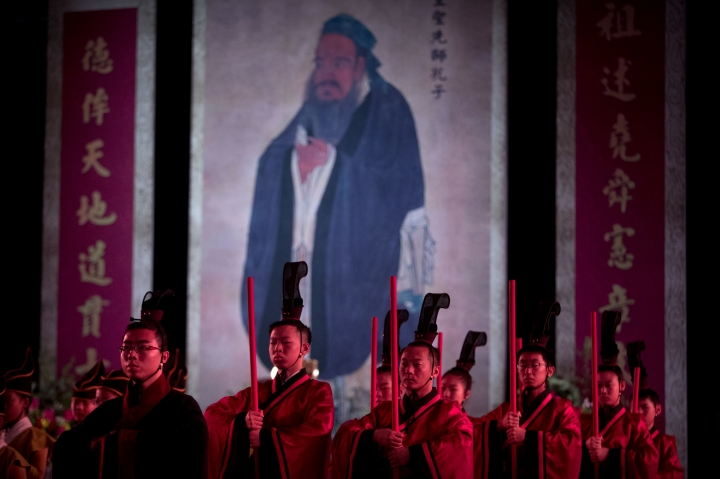 FILE - In this Sept. 28, 2016 file photo, participants in traditional dress stand near an oversized portrait of Confucius during a ceremony to observe the 2567th anniversary of his birth in Beijing. A Chinese government department announced on Monday, May 27, 2019, that China is running five-day Confucian culture immersion courses for religious leaders in the sage's hometown as part of a campaign to extend government control over faith communities through a process of sinicization. (AP Photo/Mark Schiefelbein, File)