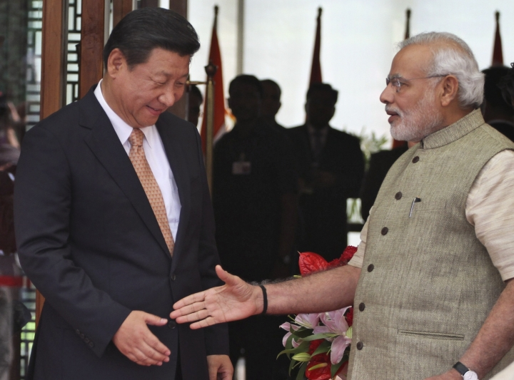 FILE - In this Sept. 17, 2014, file photo, Indian Prime Minister Narendra Modi, right, welcomes Chinese President Xi Jinping, upon his arrival at a hotel in Ahmadabad, India. Modi won a second term in office in May, 2019, by presenting a muscular image to voters by ordering an air strike inside Pakistan in response to a suicide attack on Indian paramilitary forces in troubled Kashmir ahead of national elections. India faces challenge from China as it is continuing to encircle India, carry on with the belt and road initiative and befriend its longtime rival Pakistan. But their relations have shown a thaw with Beijing recently deciding against blocking the designation of Pakistan-based Masood Azhar as a global terrorist. (AP Photo/Ajit Solanki, File)